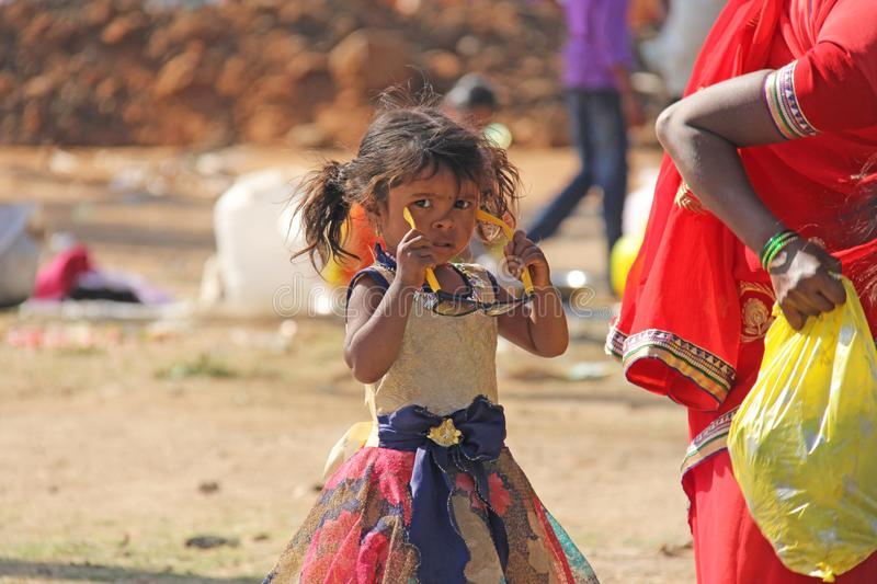 India, Hampi, 02 February 2018. A small poor and dirty Indian girl playing with sunglasses. A little girl in big glasses from the royalty free stock photos