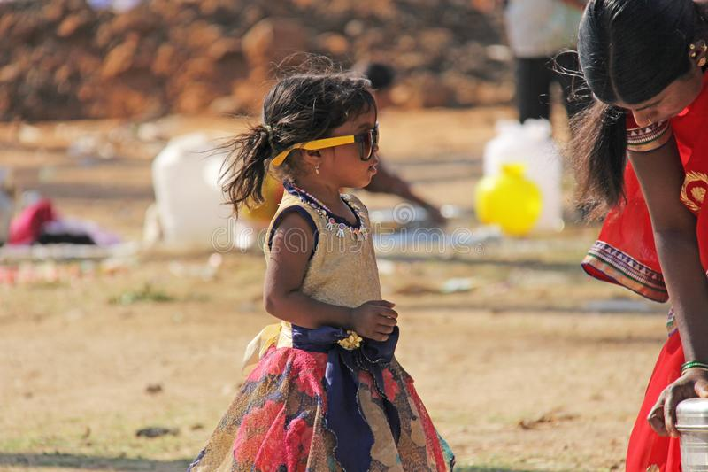 India, Hampi, 02 February 2018. A small poor and dirty Indian girl playing with sunglasses. A little girl in big glasses from the. Sun. The girl is a royalty free stock images