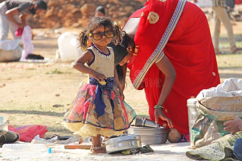 India, Hampi, 02 February 2018. A small poor and dirty Indian girl playing with sunglasses. A little girl in big glasses from the. Sun. The girl is a stock photos