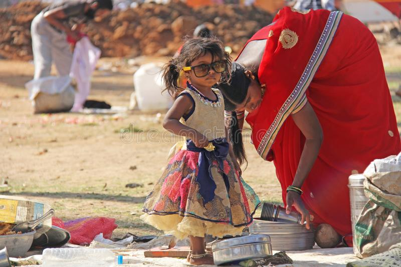 India, Hampi, 02 February 2018. A small poor and dirty Indian girl playing with sunglasses. A little girl in big glasses from the. Sun. The girl is a stock image