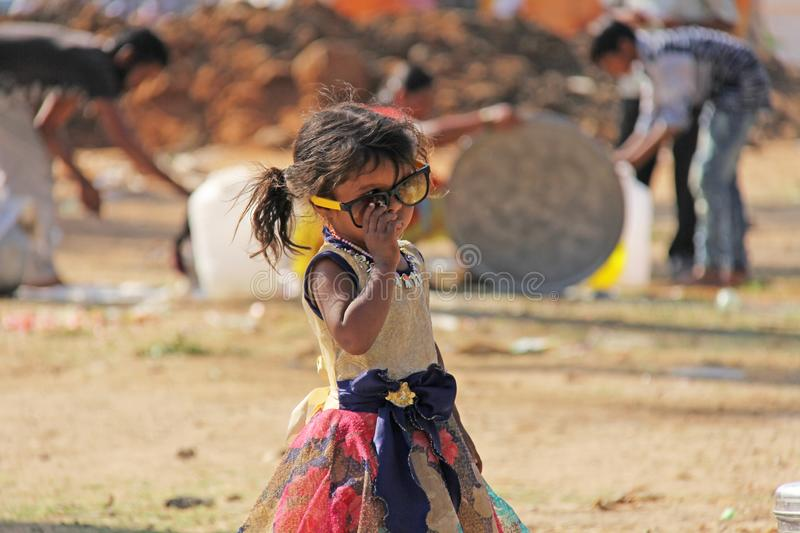 India, Hampi, 02 February 2018. A small poor and dirty Indian girl playing with sunglasses. A little girl in big glasses from the. Sun. The girl is a stock images