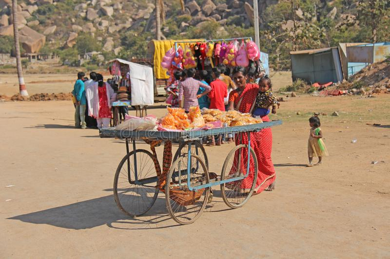 India, Hampi, 02 February 2018. Street shopping on a cart. A girl in a sari sells sweets and snacks.  royalty free stock images