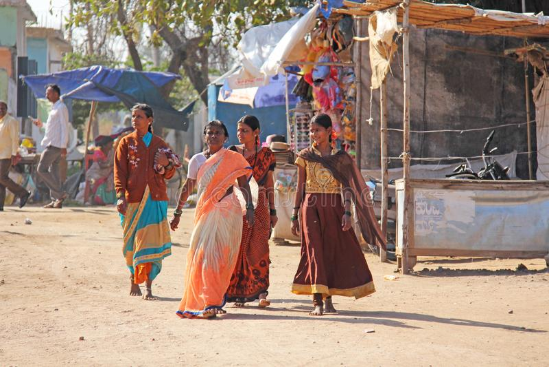 India, Hampi, 02 February 2018. Women in bright saris walk down the street and smile. Indian women. Hampi, vijayanagar, karnataka, unesco royalty free stock photography