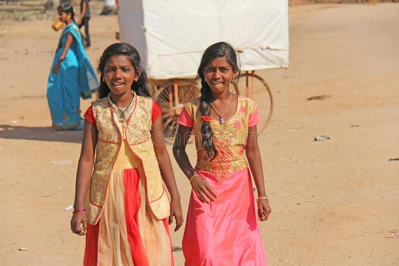 India, Hampi, 02 February 2018. Young girls in beautiful saris walk down the street and smile.  stock photo