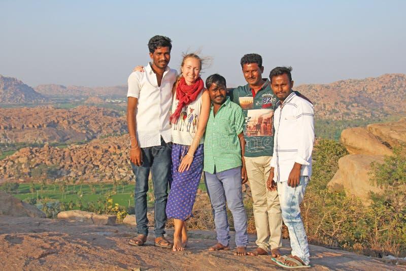 India, Hampi, 31 Januari, 2018 De mensen Hindus worden gefotografeerd met een Europees meisje met eerlijke huid en blond haar And stock afbeelding