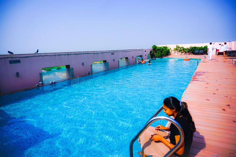 India - jaipur - hotel royal orchid - september 9, 2019, a roof top swimming pool with some people. India - jaipur - hotel royal orchid - september 9, 2019, a stock image