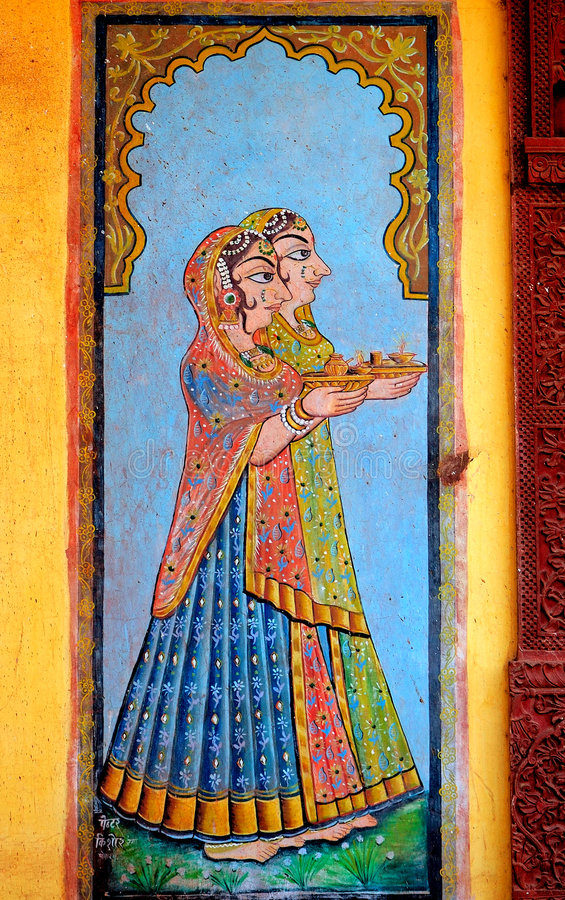 India, Jaisalmer: painting on the wall. Of a small palace; blue background and two women dressed with the typical saree royalty free stock photography