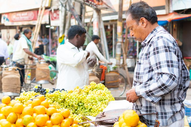 India, Varanasi, Mar 10 2019 - Unidentified vendor man sells and weighs grapes on traditional street food market.  stock photography