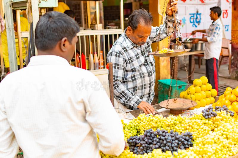 India, Varanasi, Mar 10 2019 - Unidentified vendor man sells and weighs grapes on traditional street food market.  royalty free stock images