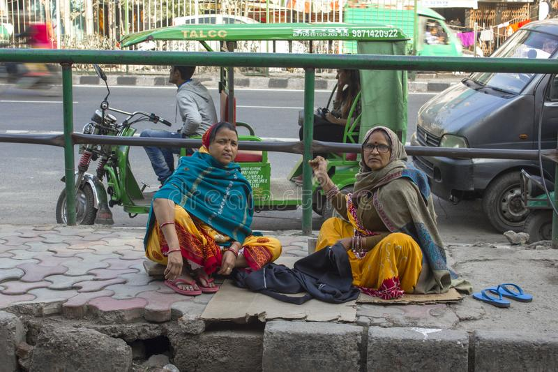 Indian adult women sew clothes sitting on the sidewalk against the backdrop of urban traffic royalty free stock photography