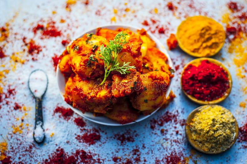 Indian appetizer dish i.e.Teekha Laal Batata or Spicy potato with all its ingredients and spices on a sliver wooden surface.This d. Famous Indian appetizer dish stock photos