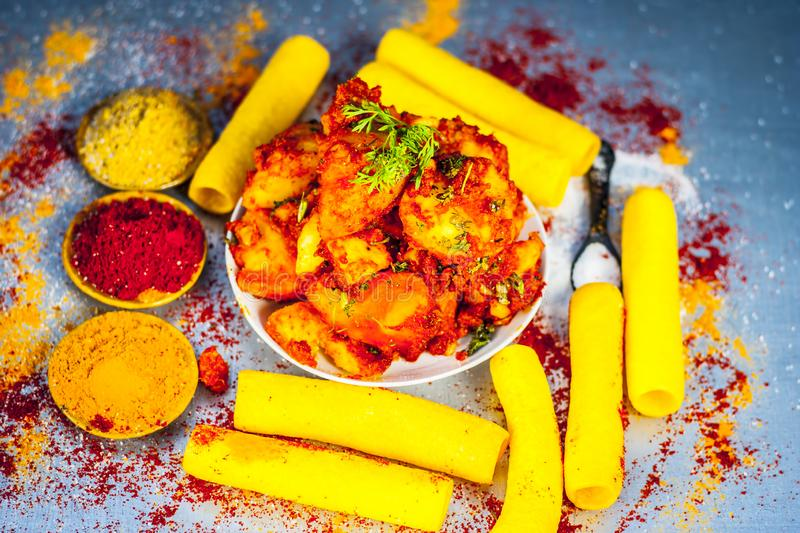 Indian appetizer dish i.e.Teekha Laal Batata or Spicy potato with all its ingredients and spices on a sliver wooden surface.This d. Famous Indian appetizer dish stock images
