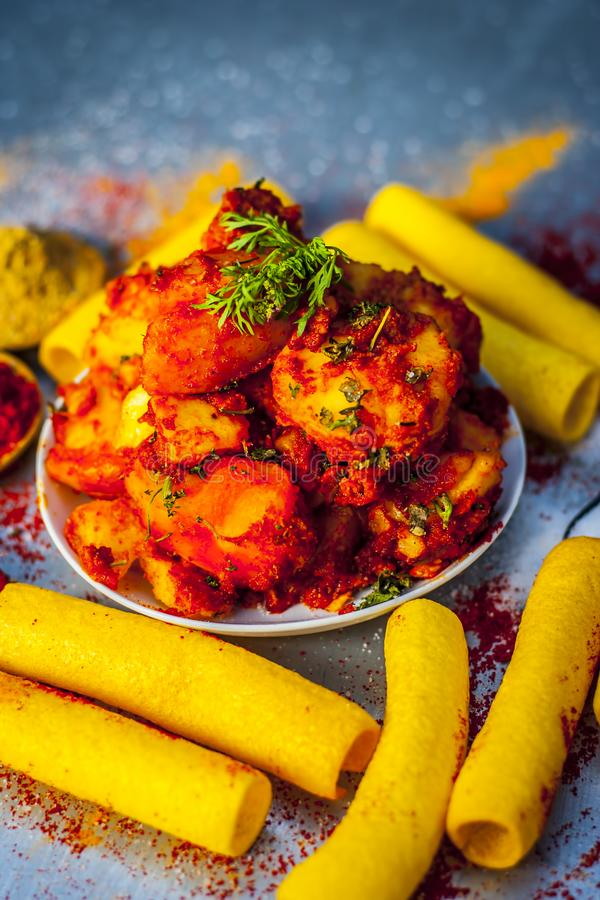 Indian appetizer dish i.e.Teekha Laal Batata or Spicy potato with all its ingredients and spices on a sliver wooden surface.This d. Famous Indian appetizer dish stock photo