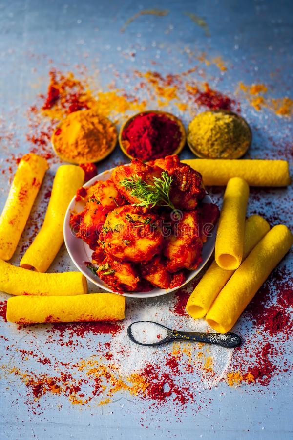 Indian appetizer dish i.e.Teekha Laal Batata or Spicy potato with all its ingredients and spices on a sliver wooden surface.This d. Famous Indian appetizer dish royalty free stock image