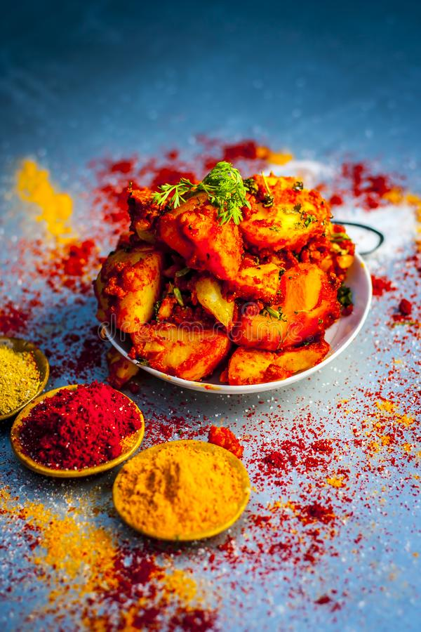 Indian appetizer dish i.e.Teekha Laal Batata or Spicy potato with all its ingredients and spices on a sliver wooden surface.This d. Famous Indian appetizer dish royalty free stock images