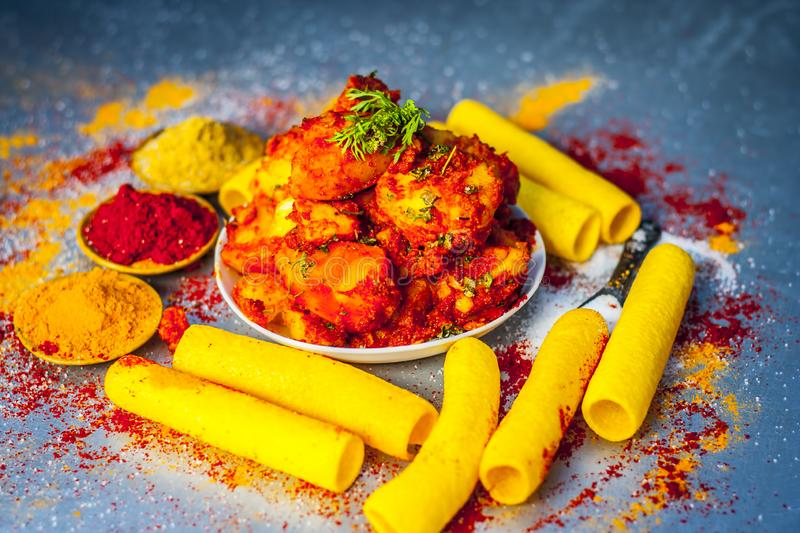 Indian appetizer dish i.e.Teekha Laal Batata or Spicy potato with all its ingredients and spices on a sliver wooden surface.This d. Famous Indian appetizer dish royalty free stock photography