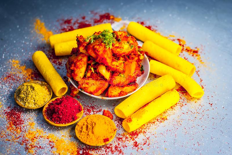 Indian appetizer dish i.e.Teekha Laal Batata or Spicy potato with all its ingredients and spices on a sliver wooden surface.This d. Famous Indian appetizer dish stock image