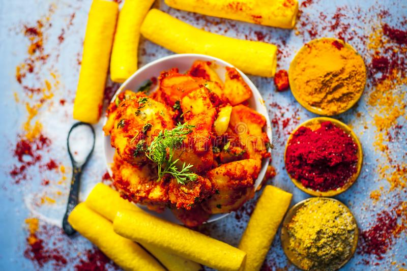 Indian appetizer dish i.e.Teekha Laal Batata or Spicy potato with all its ingredients and spices on a sliver wooden surface.This d. Famous Indian appetizer dish stock photography