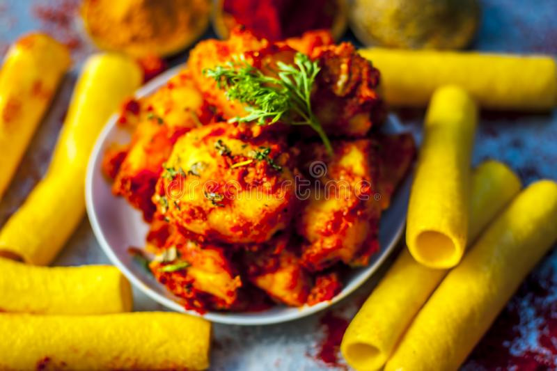 Indian appetizer dish i.e.Teekha Laal Batata or Spicy potato with all its ingredients and spices on a sliver wooden surface.This d. Famous Indian appetizer dish royalty free stock photo