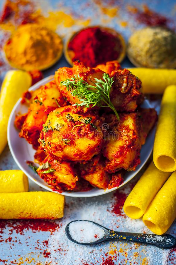 Indian appetizer dish i.e.Teekha Laal Batata or Spicy potato with all its ingredients and spices on a sliver wooden surface.This d. Famous Indian appetizer dish royalty free stock photos