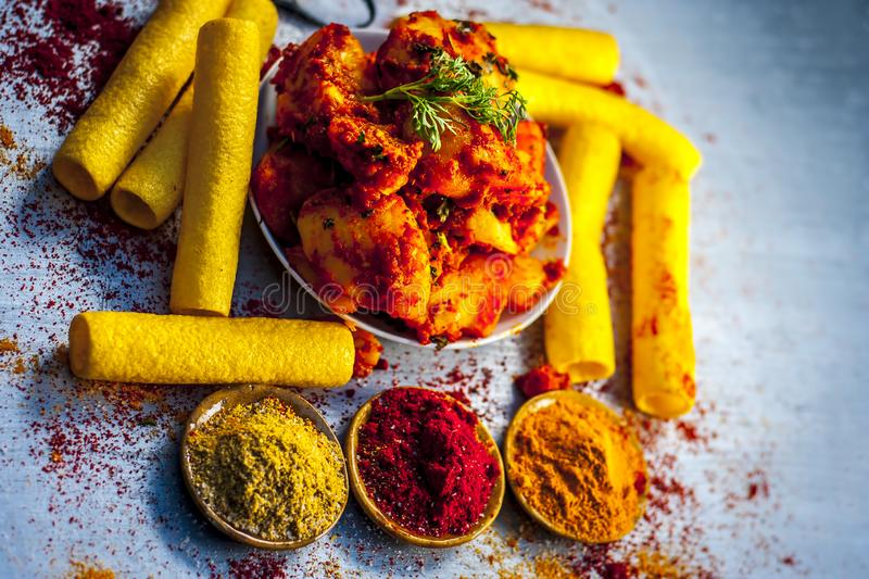 Indian appetizer dish i.e.Teekha Laal Batata or Spicy potato with  all its ingredients and spices on a sliver wooden surface.This. Dish is popularly eaten with royalty free stock photos