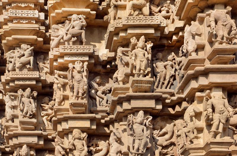 Indian architecture with figures of dancing people, gods, animals. Reliefs of historical temple in Khajuraho. royalty free stock photos