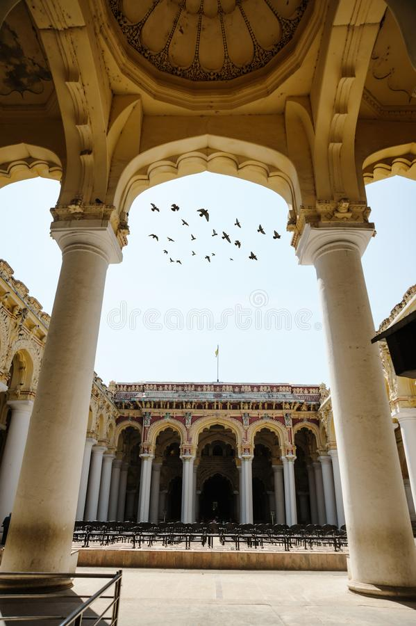 Indian architecture Thirumalai Nayakkar Mahal palace with flying birds through arch moment in Madurai. Photo of Indian architecture Thirumalai Nayakkar Mahal stock photography