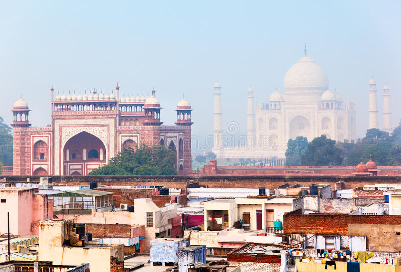 Indian architecture, view over Agra in morning mist. Residential quarter in Agra with Great gate (Darwaza-i rauza) and Taj Mahal as a backdrop royalty free stock images