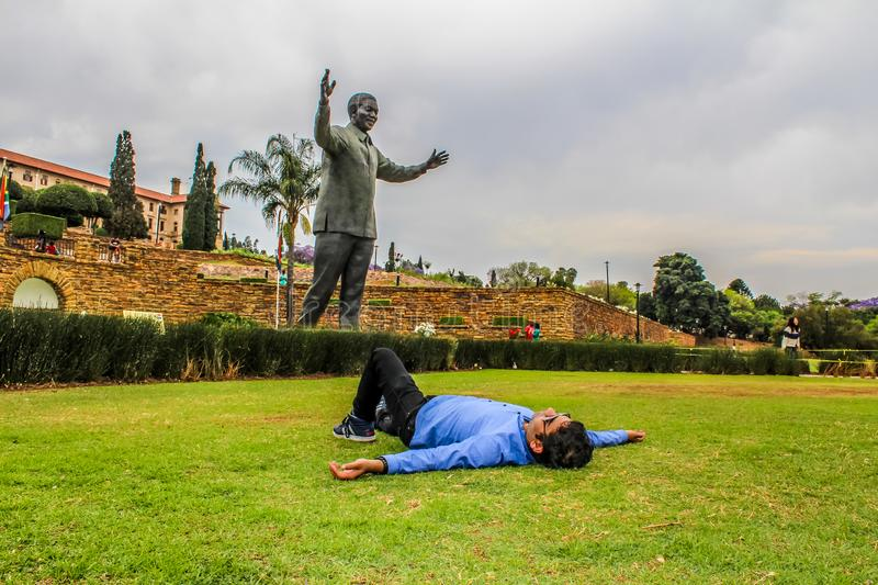 An Indian Asian young male taking rest in front of Nelson Mandela stock photo