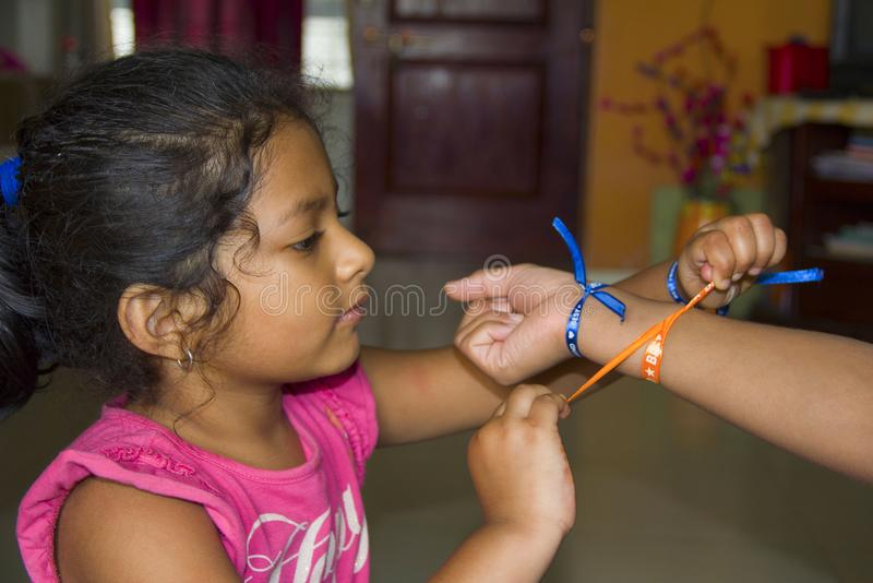Indian baby girl tying a friendship band to her friend. At Pune royalty free stock photo