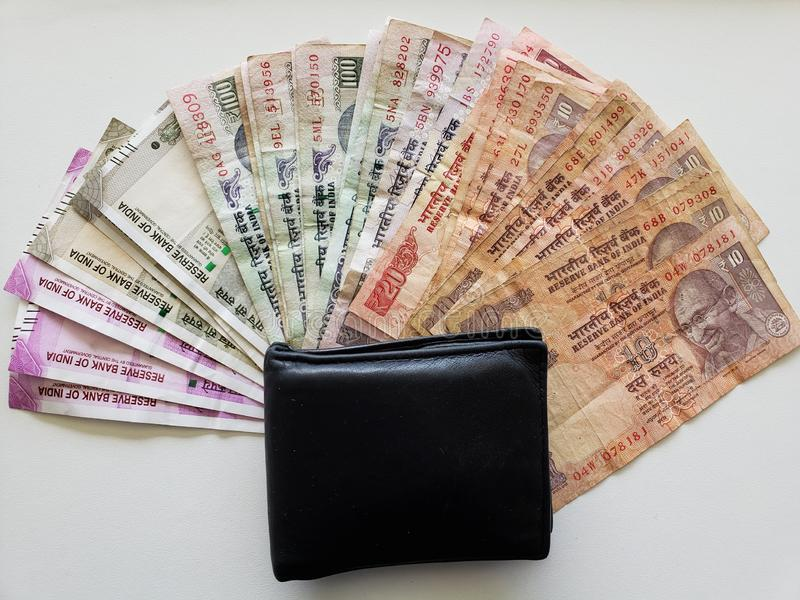 Indian banknotes of different denominations and black leather wallet stock photos