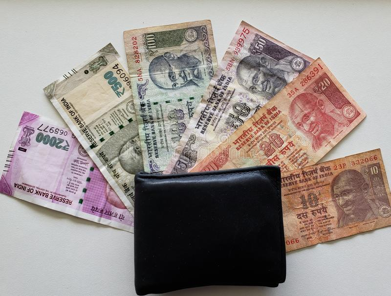 Indian banknotes of different denominations and black leather wallet royalty free stock photo