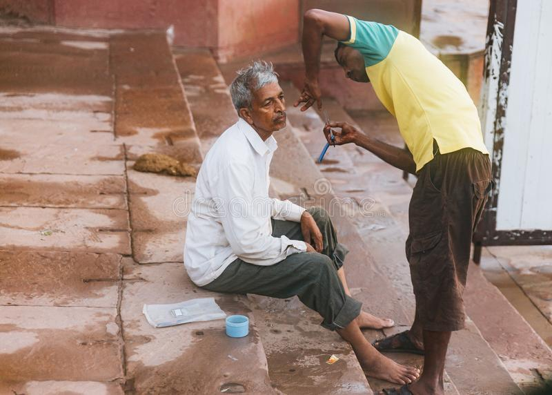The Indian barber shaves a Hindu pilgrim on the ghats. Life along the Ganges Ganga river in the morning in Varanasi. stock photos