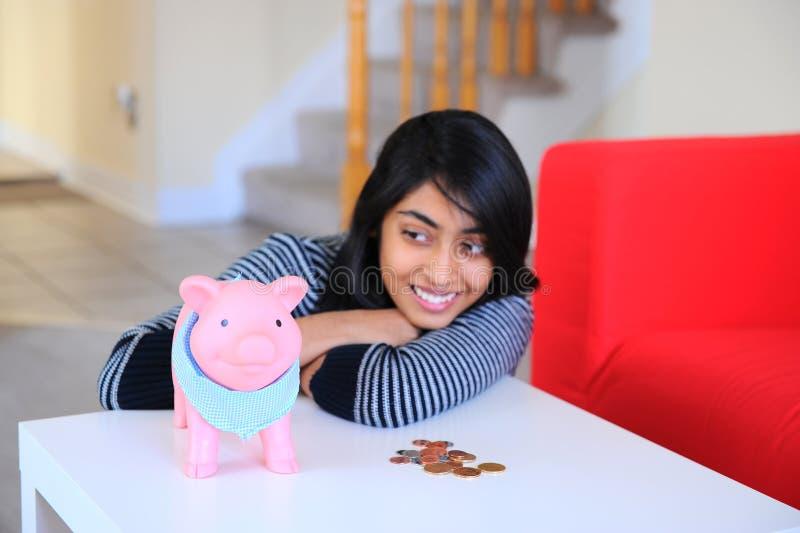 Indian beautiful girl looking to her piggybank