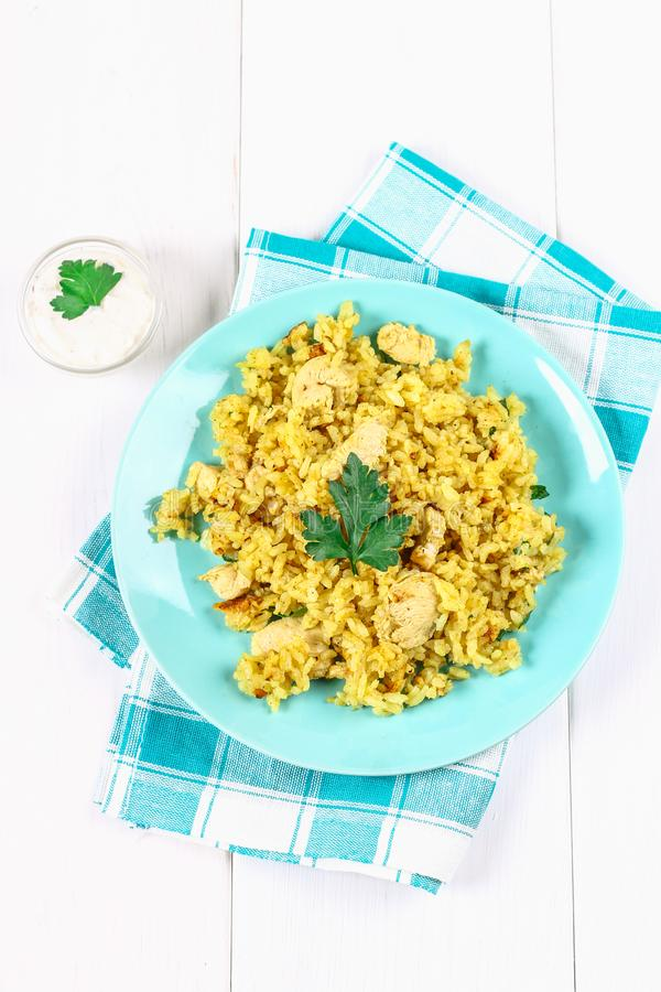 Indian biryani with chicken, yogurt and spices in a plate on a wooden table. New Year's, Christmas dish. Indian biryani with chicken, yogurt and spices in a stock photo