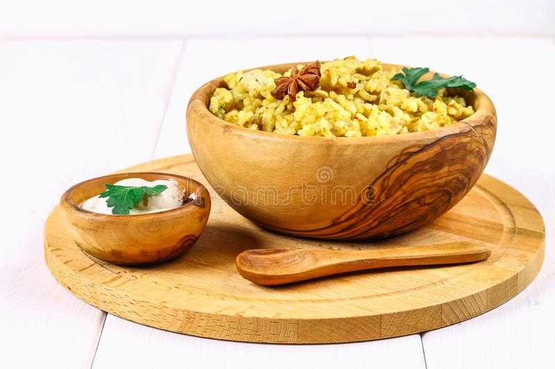 Indian biryani with chicken, yogurt and spices in a plate on a wooden table. New Year's, Christmas dish. Indian biryani with chicken, yogurt and spices in a royalty free stock image