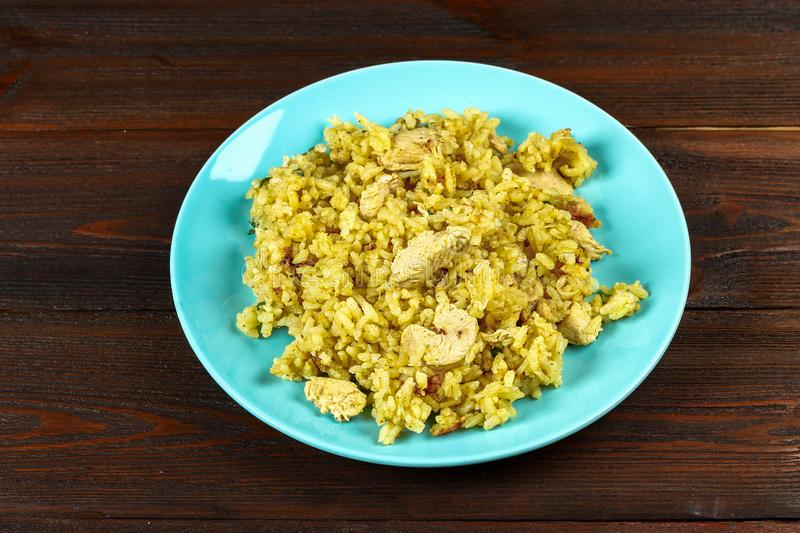 Indian biryani with chicken, yogurt and spices in a plate on a wooden table. New Year's, Christmas dish. Indian biryani with chicken, yogurt and spices in a royalty free stock images