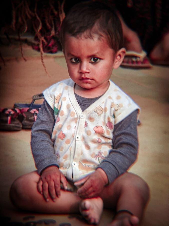 Indian blonde baby sitting on the ground. Village, uttar pradesh, india, bareilly, Homo sapiens, Bright eyes, black hairs stock photo