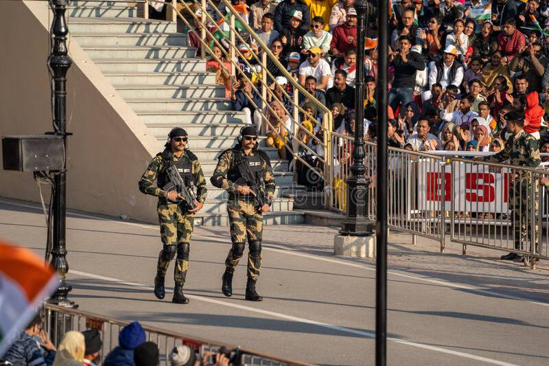 Indian Border Security Force men with large machine guns and camo walk in the Wagah Border. Amritsar India - Febuary 8, 2020: Indian Border Security Force men royalty free stock photos