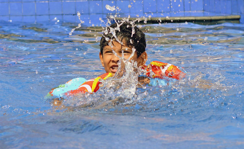 Asian Indian boy practicing Swimming in his summer camp. An Indian boy of age 6-7 years enjoying his summer holidays during his swimming practice session in a royalty free stock photography