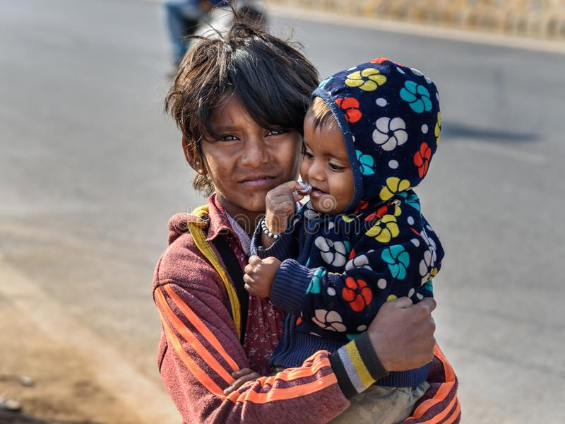 Indian boy with child on the street. Poor people come with family to the city from the village for work. And they living in the. Ajmer, India - February 07, 2019 royalty free stock photography