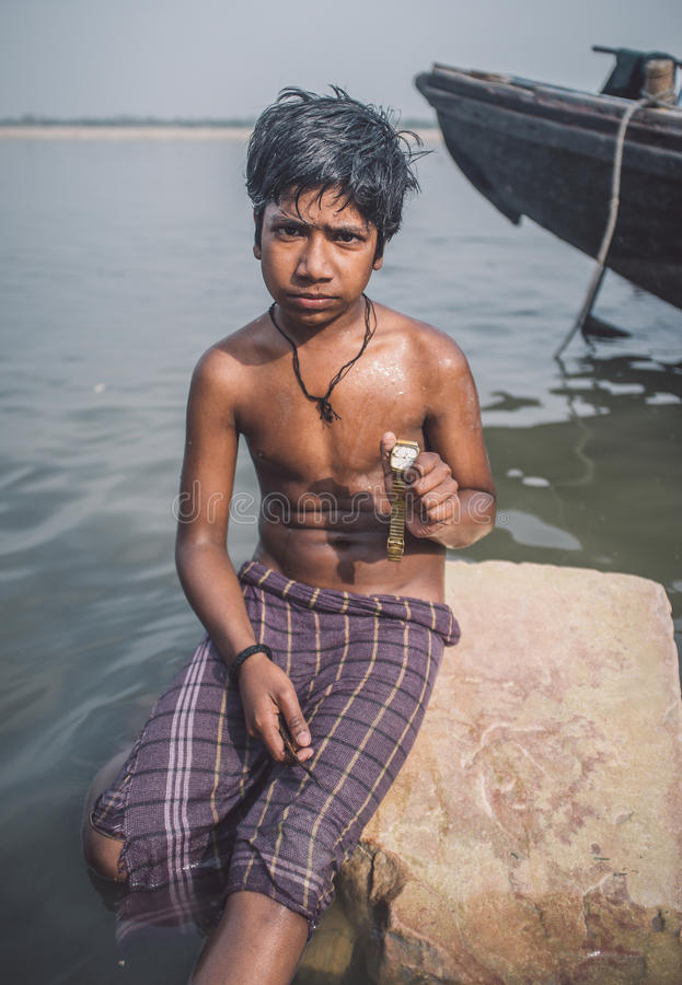 Indian boy with watch. VARANASI, INDIA - 25 FEBRUARY 2015: Indian boy sits shirtless on rock in Ganges river and shows watch he found. Post-processed with grain royalty free stock images