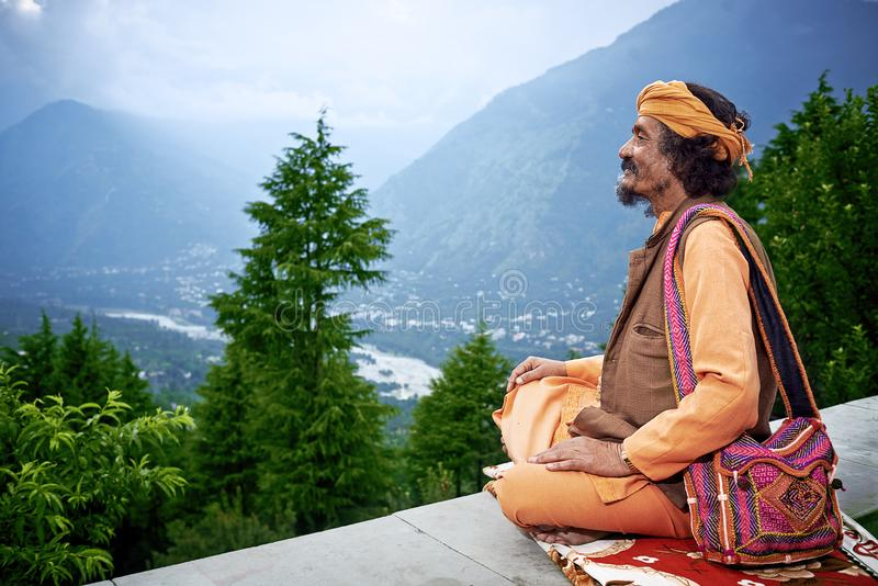 Indian Brahmin looks to the valley Kullu. Naggar, INDIA - JULY 17: Indian Brahmin looks down from himalaya mountains to the valley Kullu. July 17, 2013 in Naggar royalty free stock photography