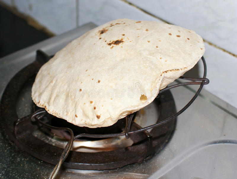 Indian bread,Roti, being blown over oven stock photography