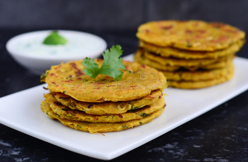 Indian breakfast consisting of parantha and curd. Stack of Indian Parantha or roti (stuffed Indian bread) a plate and yogurt breakfast royalty free stock photography