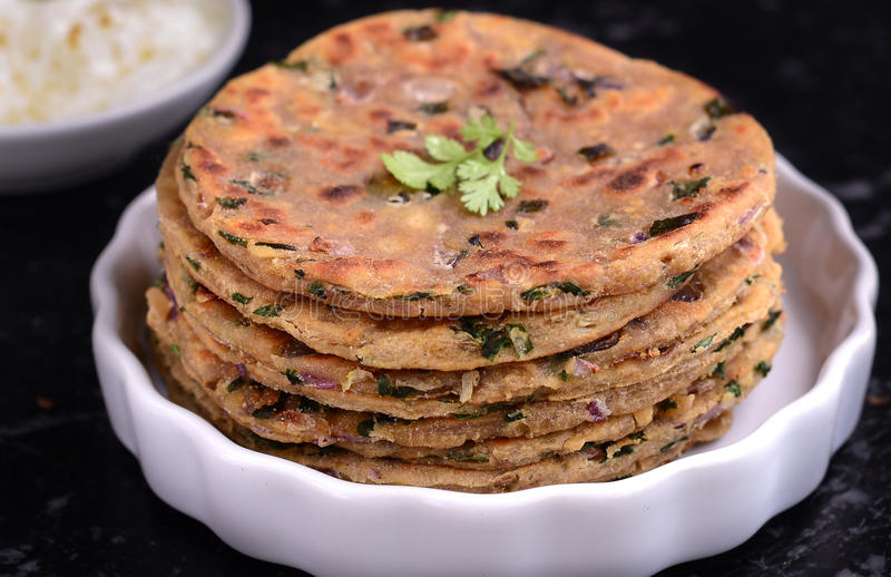 Indian breakfast consisting of parantha and curd. Stack of Indian Parantha or sindhi koki(stuffed Indian bread) a plate and yogurt breakfast royalty free stock images