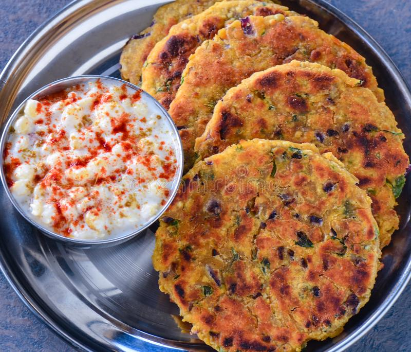 Indian breakfast koki flatbread with raita yogurt dip. Fried, onion, cool, travel, summer, lunch, dinner, brekkie, steel, plate, south, sindhi, punjabi stock images
