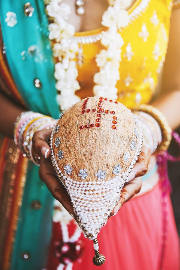 Indian bride with bangles on her wrist holding coconut shagun nariyal for indian marriage ritual stock photos