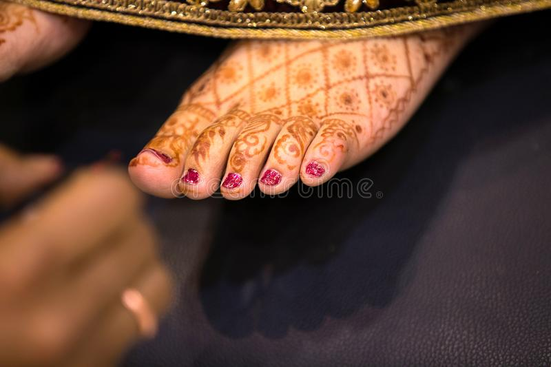 Indian bride feet coloring with indian henna paste or mehndi design of symbolic tattoos during a. Hindu wedding ceremony - Image royalty free stock images