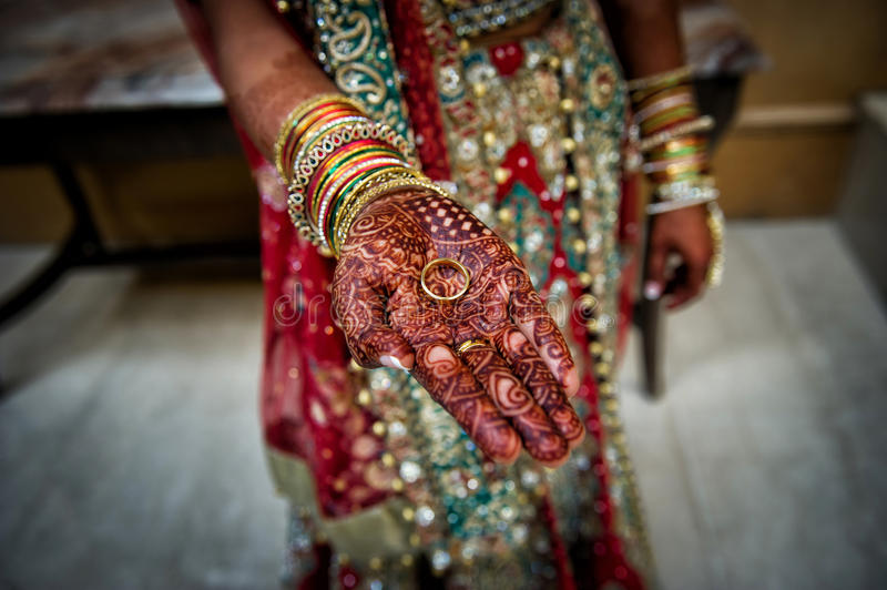 Indian bride henna hand holding grooms ring stock photos